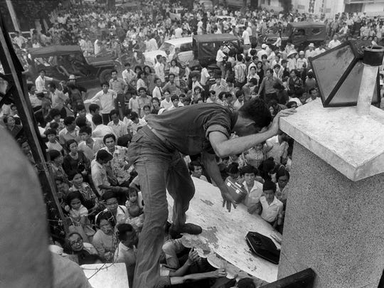 In this April 29, 1975, file photo, South Vietnamese civilians try to scale the 14-foot wall of the U.S. embassy in Saigon, trying to reach evacuation helicopters as the last Americans departed from Vietnam. More than two bitter decades of war in Vietnam ended with the last days of April 1975.