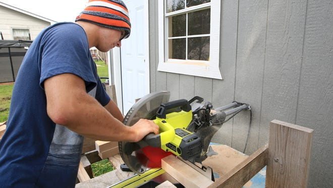 Stone Ducimetiere uses his miter saw to trim maple wood into smaller pieces Friday morning. Ducimetiere began his own business called Stone's Sticks, which repurposes discarded wood.