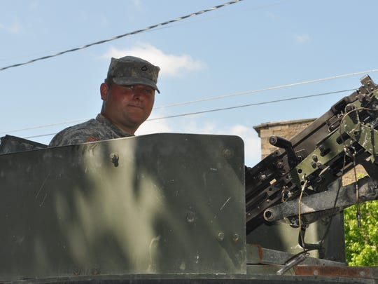 National Guard Pfc.Ethan Scott sits at the helm of an M2 50-caliber machine gun, mounted on a Humvee, during a memorial service on Dryden's village green.