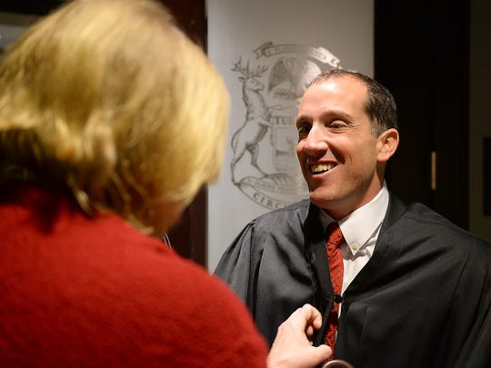 Court adminisrative specialist Lynn Seaks helps Richard Bernstein, who is blindd, put on his robe before entering the courtroom Jan. 5.