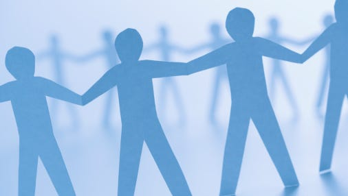 A stock image of cutout paper men holding hands.