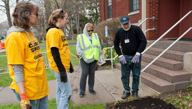File photo: Heather Alford, Althea Merryman and Kathy Strauss, all of Rochester, and librarian Paul Tantillo plant a garden at the Rochester Public Library branch in Charlotte during the 2014 Clean Sweep.