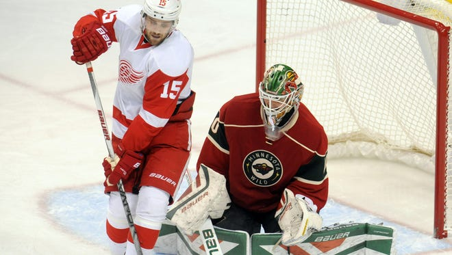 Red Wings forward Riley Sheahan redirects the puck as Wild goalie Devan Dubnyk (40) sets up to make the save during the third period of the Wings' 3-1 loss Monday in St. Paul, Minn.