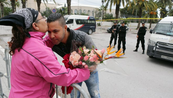 A Tunisian woman kisses a plainclothes policeman in Tunis, Tunisia, Nov. 25 as she pays tribute to people killed in a bomb attack on a bus transporting presidential guards a day earlier.