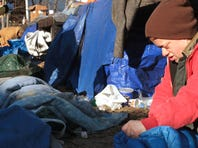 """Lyzz Buford rolls up her sleeping bag as she moves out of a homeless camp on East Phelps Street with assistance from volunteers on Saturday. The move was prompted by the police, who gave them 24 hours to vacate. Buford has been homeless for five years. """"This was one of the best spots I've been in,"""" she said."""