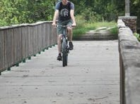 A bicyclist rolls along the historic Frisco Highline Trail bridge over the Little Sac River, rebuilt by Ozark Greenways after it was torched by an arsonist in 2006. The trail marks its 20th anniversary this summer.