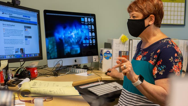 Gina Millsap, CEO of the Topeka and Shawnee County Public Library, reviews articles in her office Friday that she has written regarding the need for broadband coverage. Millsap, who lives outside Auburn, often comes into her office for a faster internet connection than she gets at home.
