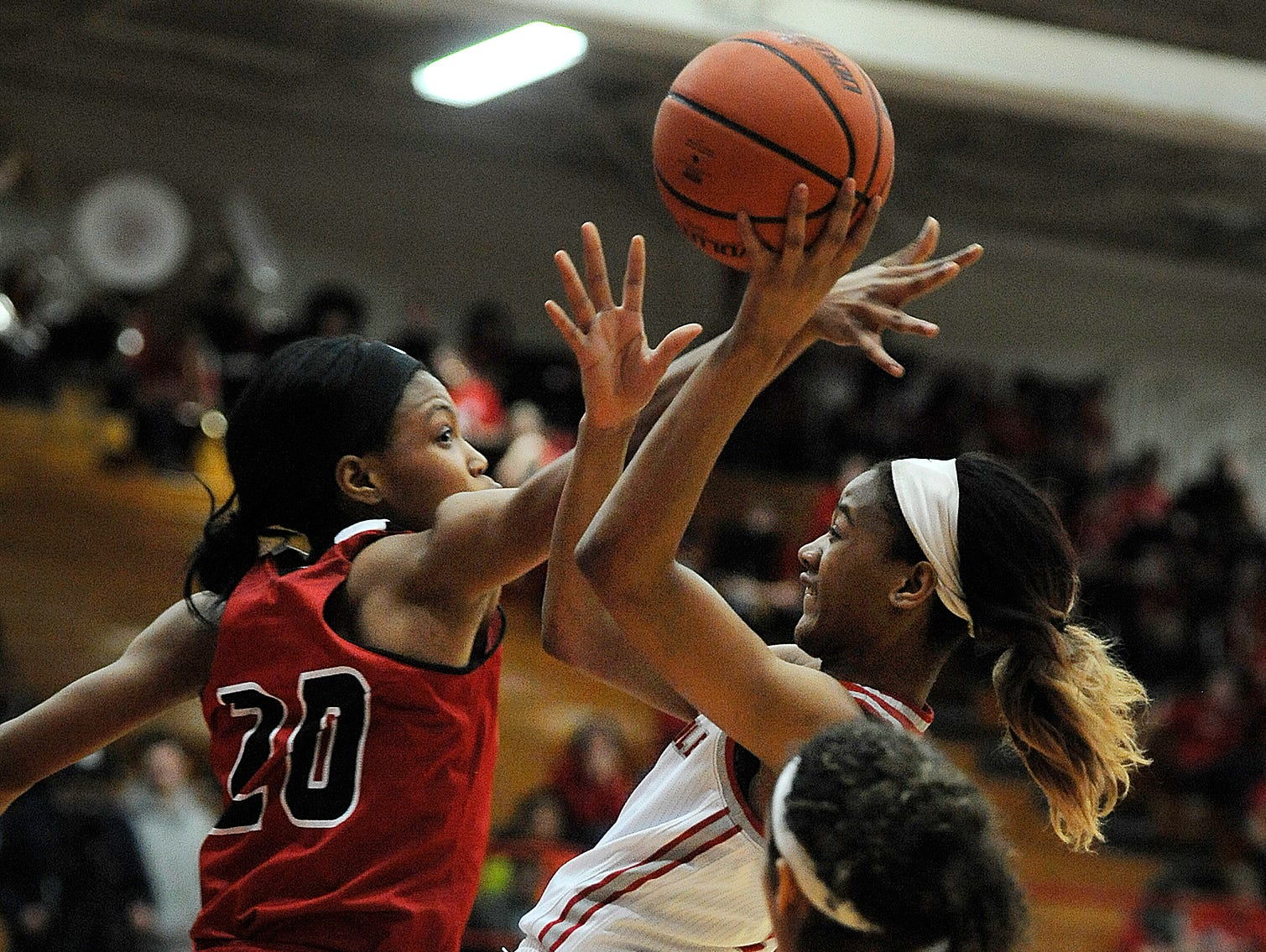 New Albany's Chyna Anthony (20) defends against the shot of Jeffersonville's Jhala Henry (center) on Friday at Jeffersonville High School. Jan.20, 2017