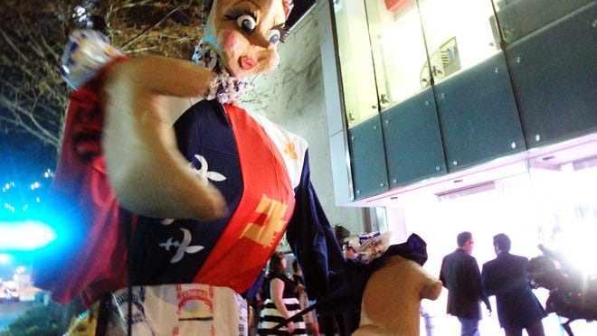 A giant figure puppet designed by artists with Wanderlust Theatre Co., this year's Festival International street animation artists, greets guests as they arrive to La Fete du Festival, a fundraiser and pin and poster unveiling for the 2015 Festival International de Louisiane, Thursday, December 4, 2014, at the Acadiana Center for the Arts in Lafayette, La.