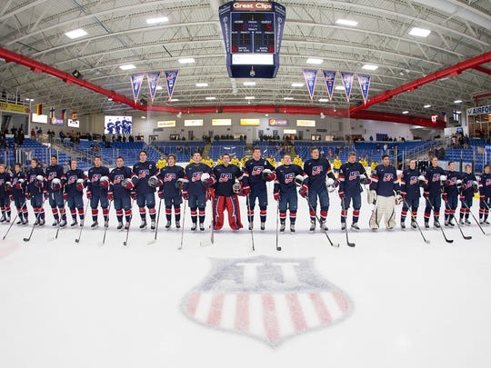 "With the logo honoring the late Jim ""J.J."" Johannson front and center, Team USA and Sweden stand and listen to the U.S. national anthem after a Five Nations Tournament game earlier this year."