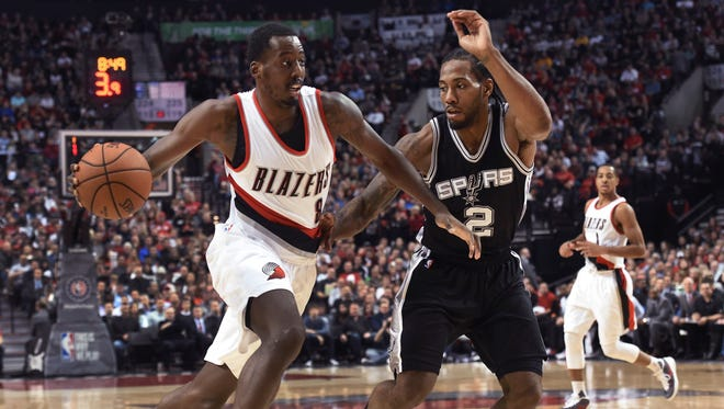 Portland Trail Blazers forward Al-Farouq Aminu (8) drives to the basket on San Antonio Spurs forward Kawhi Leonard (2) during the first quarter of an NBA basketball game in Portland, Ore., Wednesday, Nov. 11, 2015.