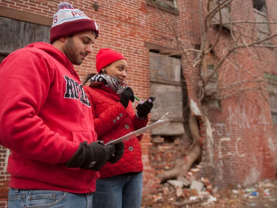 Zaid N. Mazahreh of Cherry Hill, left, and Rutgers student Danielle Davis survey buildings and lots in Cramer Hill as they collect data for the Rutgers University-Camden's Center for Urban Research and Education (CURE) interactive website, a micro-view of Cramer Hill in East Camden. 02.04.15