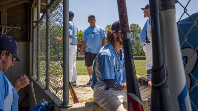 Peoria head coach Mike Olson, 71, background center, gathers with his players at the dugout before the start of a Kickapoo Valley League baseball game last year in Cuba. Olson's Peoria team is among those scheduled to play a small selection of games this summer. [DAVID ZALAZNIK/JOURNAL STAR