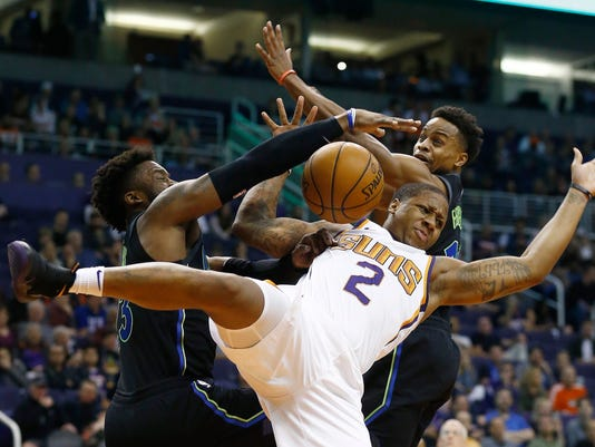 Phoenix Suns guard Isaiah Canaan (2) is fouled by Dallas Mavericks guards Wesley Matthews, left, and Yogi Ferrell, right, during the first half of an NBA basketball game Wednesday, Jan. 31, 2018, in Phoenix. (AP Photo/Ross D. Franklin)