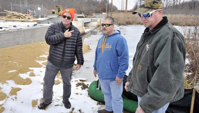 Nearby property owner Jack Tomb (left) standing in the place where Dave Holloway (center) and Chris Whitehead used to launch their small boats to hunt and fish on Dragon Run near St. Georges. GARY EMEIGH/Special To The News Journal