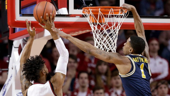 Michigan's Charles Matthews grabs the rim as he tries to block Nebraska's Isaac Copeland during the first half in Lincoln, Neb. on Thursday.