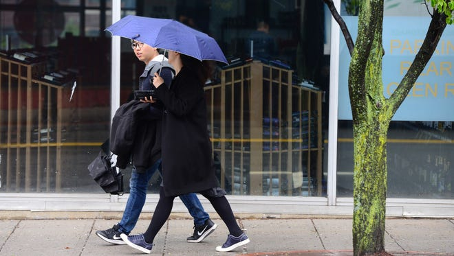 A woman carries an umbrella as light rain falls in Rutherford Wednesday morning April 26, 2017.