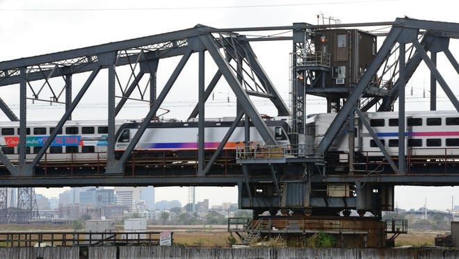 Two NJ Transit trains cross paths on a swing bridge that will be replaced on the Hackensack River. U.S. Senators Cory Booker and Bob Menendez, Gov. Chris Christie, Gateway Program Development Corporation Chairman Richard Bagger and Amtrak Chairman Tony Coscia recently took part in a ground breaking ceremony.