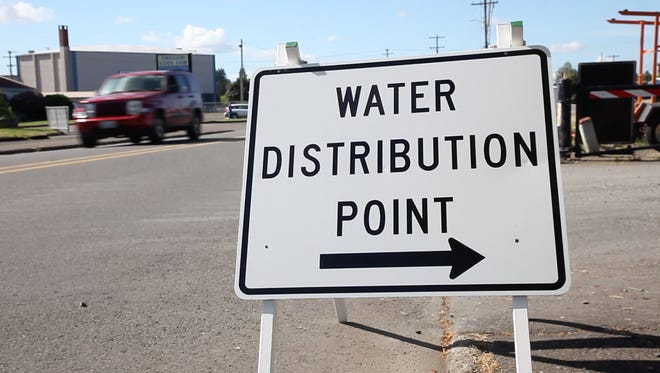 A sign points to one of the water distribution points at the Oregon State Fairgrounds Friday morning, June 1, 2018, in Salem, Oregon. Residents were filling up jugs to the 5-gallon limit, shoring up their drinking water reserves. There are seven locations that will be open around the clock until the water advisory is lifted.(KELLY JORDAN / Statesman Journal)