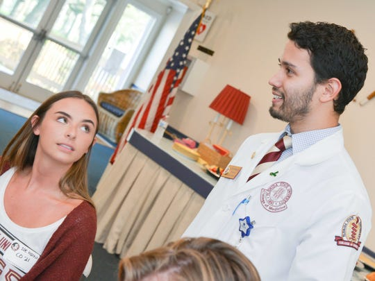 Florida State University students Zoe Harris and Daniel Farinas Lugos  answer questions at the Fort Pierce Yacht Club. Lugos is in the Medical School at FSU.