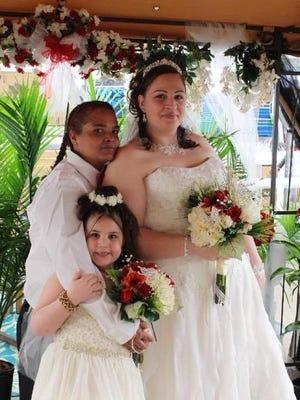Leida Torres (left) and Chrissy Slonaker Torres pose after their wedding with Slonaker Torres's daughter.