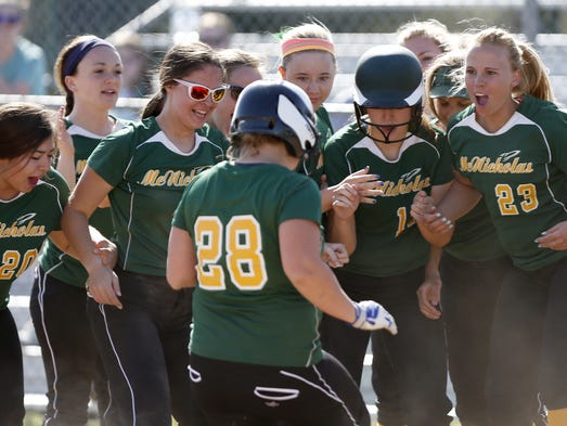 McNicholas' Katie St. Charles is swarmed by teammates after her fourth inning home run against Turpin.