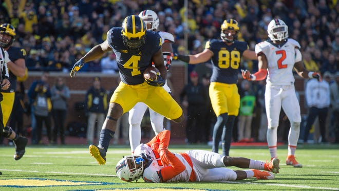 Michigan running back De'Veon Smith leaps over Illinois defensive back Stanley Green for a second quarter touchdown.