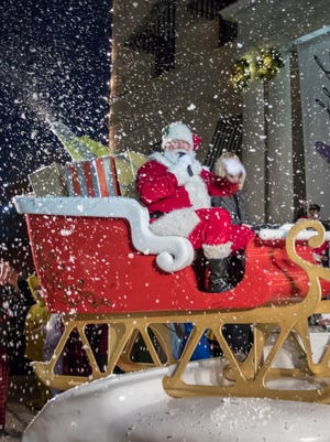 Santa waves to the crowd as snow falls in Plaza Wonderland following the annual Elf Parade in downtown Pensacola on Friday, November 24, 2017.