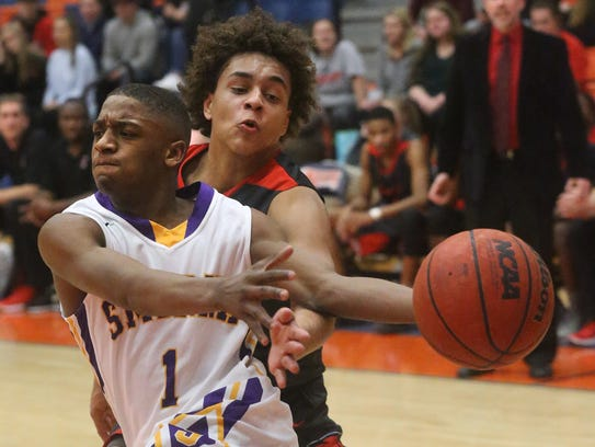 Smyrna's Tae Brady (1) pushes toward the basket as
