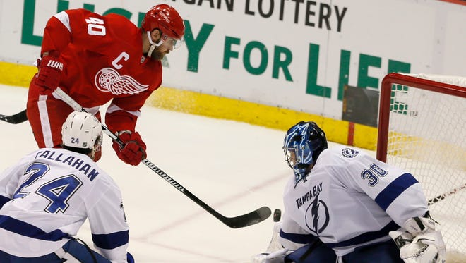 Tampa Bay goalie Ben Bishop makes a save against Red Wings forward Henrik Zetterberg as Tampa Bay's Ryan Callahan defends during the third period of the Wings' 5-2 loss Monday.