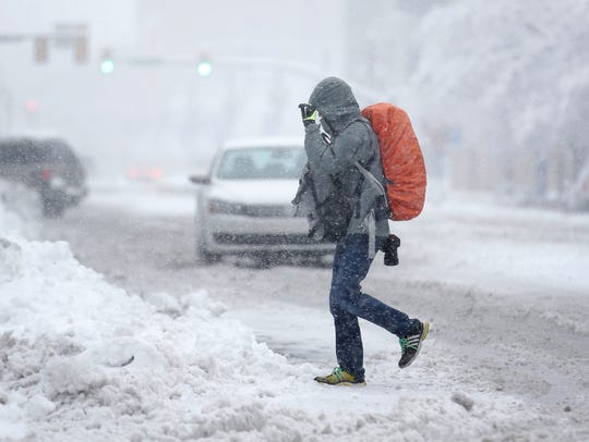 A person crosses a snowy street in this file photo dated Monday, Dec. 14, 2015.