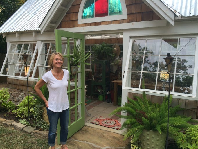 Leslie Coleman stands outside the greenhouse built