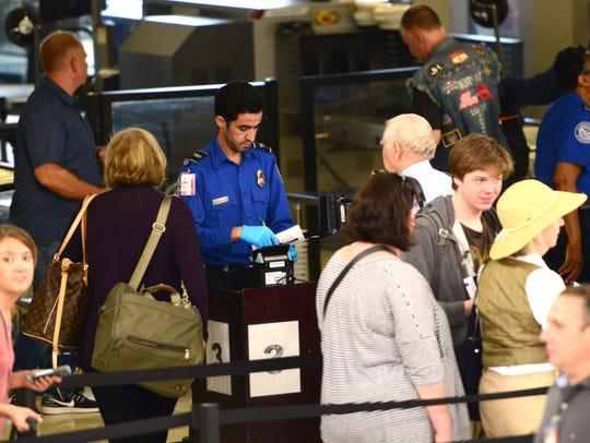 Passengers go through the TSA checkpoint in Terminal