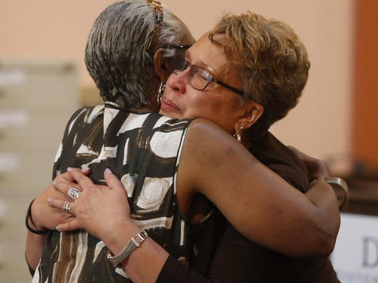 """Dr. Patrice Gilliam-Johnson (facing camera) shares a hug with documentarian Jeanne Nutter following a showing of the latest """"Voices of the Elders"""" documentary on James H. Gilliam Sr. at the Delaware Historical Society research library in Wilmington."""
