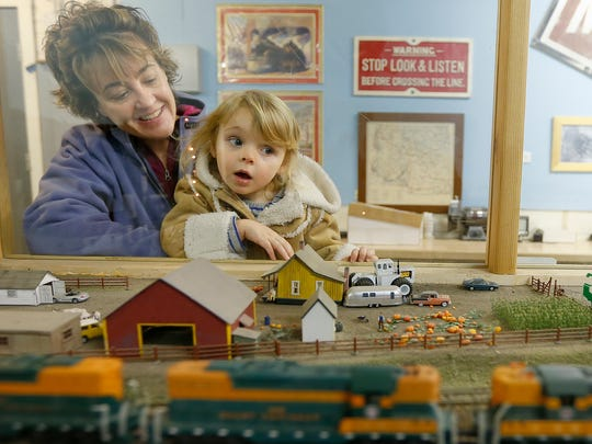Christine Ward holds her granddaughter, Gemma Moore, 3, so she can get a better look of an HO scale model train going by during a previous Great Falls Model Railroad Club's Christmas Fun Run at the Montana ExpoPark.