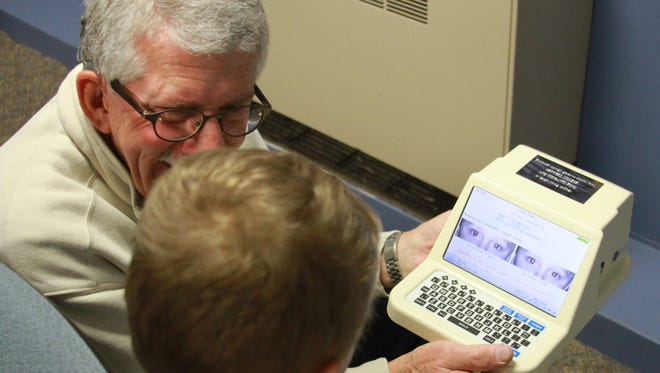Larry VanErsvelde, Grinnell Lions Club, shows a student the pictures of his eyes taken by a computerized camera at an eye screening at Fairview Elementary, Grinnell, on Thursday, Jan. 19.