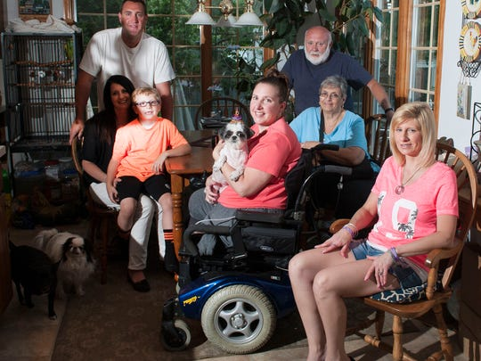 Tina Elliot, center, poses for a photo with her family, from left, Cole Elliot, Dawn Elliot, holding Cole, Steve Elliott, Tina's Brother, Sonny Elliot, Tina's father, Eileen Elliott Tina's mother, and Donna Griffin, Tina's Sister. Tina lost both legs after contracting strep throat and the flu this winter.