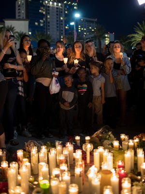 Mourners attend a candlelight vigil at the corner of Sahara Avenue and Las Vegas Boulevard  for the victims of Sunday night's mass shooting.