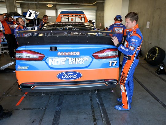 Ricky Stenhouse Jr. looks over his car during the first