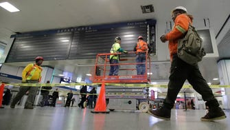 Workers replacing the train status board at Penn Station on Monday.