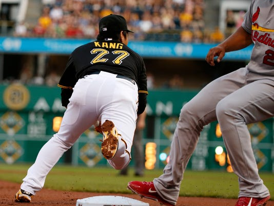 Pittsburgh Pirates third baseman Jung Ho Kang (27) makes the second out of a triple play against St. Louis Cardinals' Jhonny Peralta, right, in the second inning of a baseball game in Pittsburgh, Saturday, May 9, 2015. Cardinals' Yadier Molina hit a line drive to Walker that he caught for the first out, then Walker threw to third to get the second out against Peralta then Pirates third baseman Jung Ho Kang threw back to Walker at third to complete the triple play. (AP Photo/Gene J. Puskar)