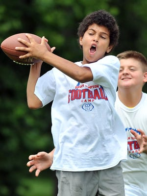 Trae Page, 11, of Lancaster, catches a ball during the Brian Sampson Memorial Youth Football Camp in Lancaster. The free camp is an annual event put on by Cordle Cares, the foundation of NFL free agent and Lancaster High School graduate Jim Cordle.