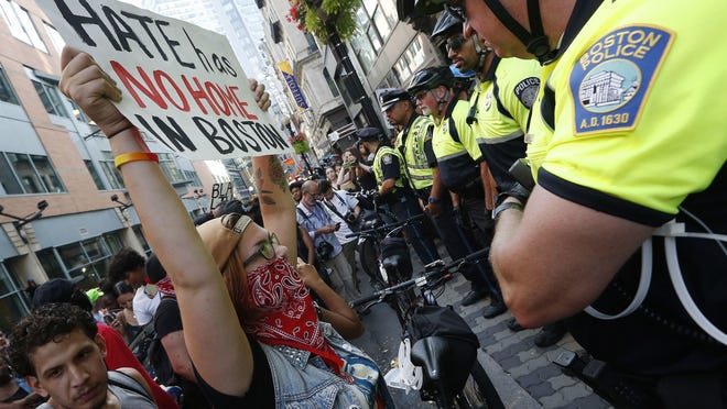 """A small group of counterprotesters who remained on the street hours after a """"Free Speech"""" rally was staged by conservative activists, face off against police, Saturday, Aug. 19, 2017, in Boston. (AP Photo/Michael Dwyer)"""
