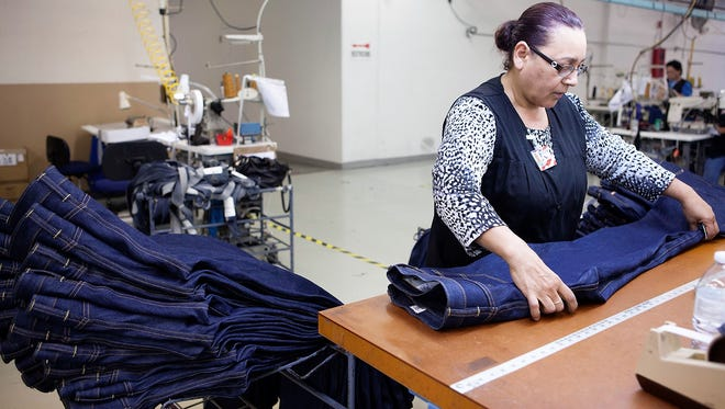Antonia Carbajal, a worker in the for-profit garment factory of ReadyOne Industries in East El Paso, folds jeans made at the plant.