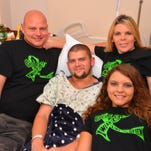 """Gaige Robbins of Melbourne is diagnosed with  nonHodgkins Lymphoma and has been undergoing chemo and radiation treatments.  His family is selling shirts that say """"Gaige. I wear lime green"""" in honor of their 19-year-old son. Gaige surrounded by his family-  his dad Shane, mom Christa and sister Kaylie."""