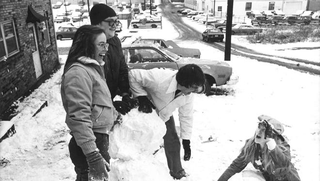 Donna Linton, Stan McCormick, Johnny Dowlen and Liz Cartwright try to build a snowman at 211 N. Fifth St. in Clarksville on Feb. 10, 1980.