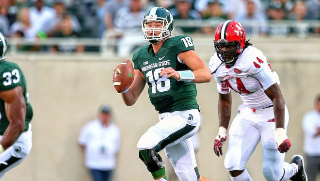 Connor Cook scrambles out of the pocket against Jacksonville State at Spartan Stadium.