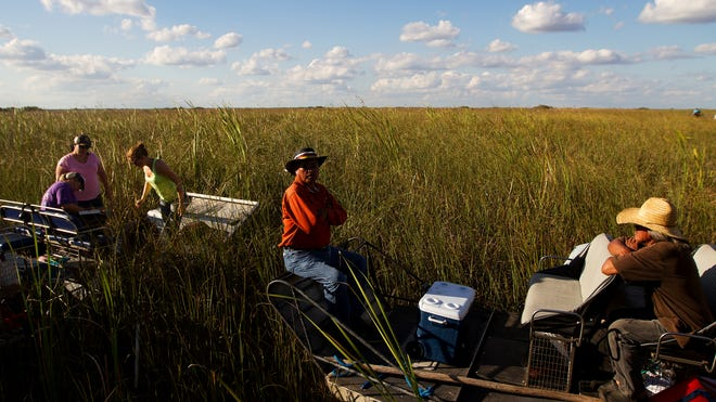 Michael C. Frank, center, and Cory Osceola, right, both members of the Miccosukee tribe take a break while scientists collect samples for an annual water quality study in the River of Grass in one of the most remote parts of the Florida Everglades.