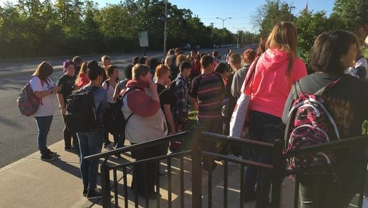 About 50 Richmond High School students gather in front of the administration building Monday morning to protest Richmond Community Schools' new policy prohibiting carrying backpacks to class.