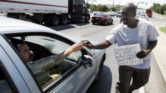 Panhandler Albert Perkins in this file photo from August 2012 accepts money on Memorial Boulevard near the intersection of Broad Street. The Murfreesboro City Council recently approved an ordinance making it illegal for panhandlers to accept money from people in vehicles. The previous ordinance also prohibited panhandlers from stepping into streets to accept money.